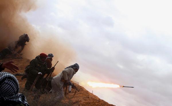 Las fuerzas rebeldes anti-gobierno libio lanzan un misil a los combatientes leales a Jaddafi.