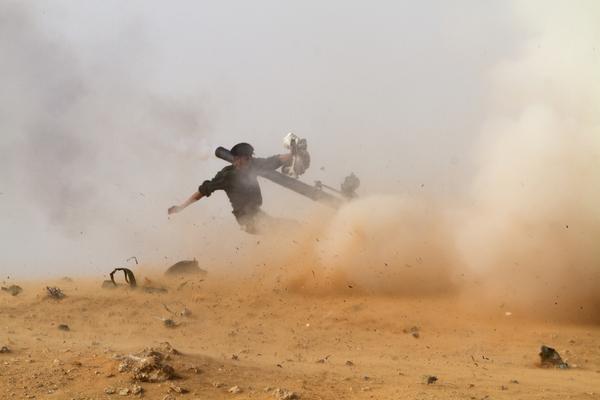 Un combatiente libio anti-gobierno apunta su arma ante el acercamiento de las fuerzas pro-Jaddafi (2011)