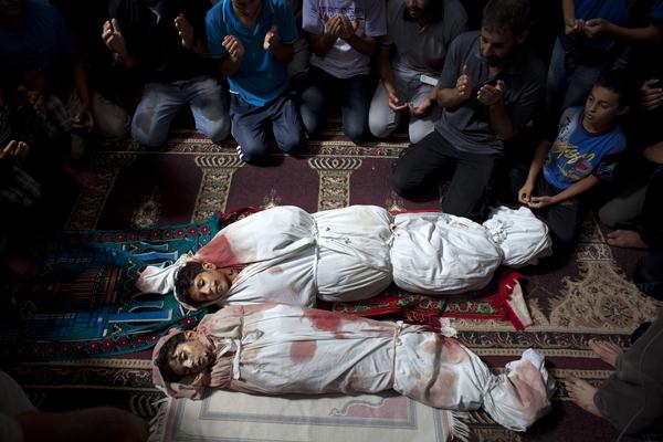 Miembros de una familia rezan en la Mezquita de Sajeria junto a los cuerpos de Amir (15), Mustafa Arief y Mohammed durante su funeral en Sajeria, Gaza, en julio del 2014.