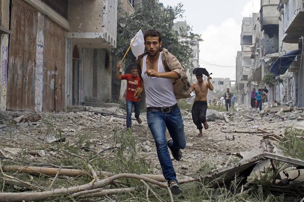 Hombres palestinos corren con una bandera blanca en el bombardeado barrio de Shejaiya, Gaza (2014)
