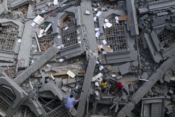 Los palestinos recogen libros religiosos musulmanes entre los escombros de la mezquita Al-Qassam, en la Franja de Gaza (2014)