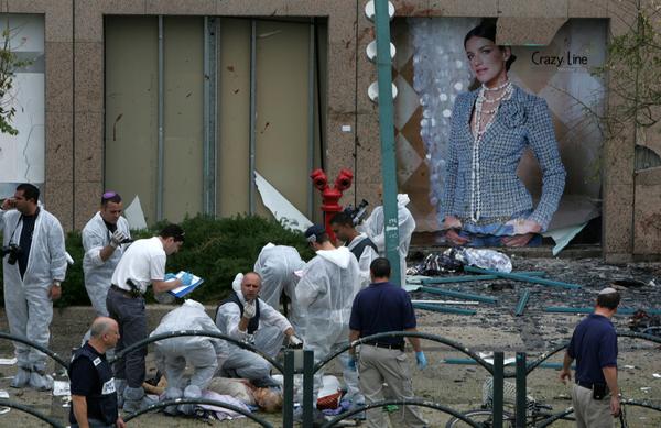 La policía israelí trata de identificar a las víctimas de un atacante suicida fuera de un centro comercial en Netanya (Israel, 2005).