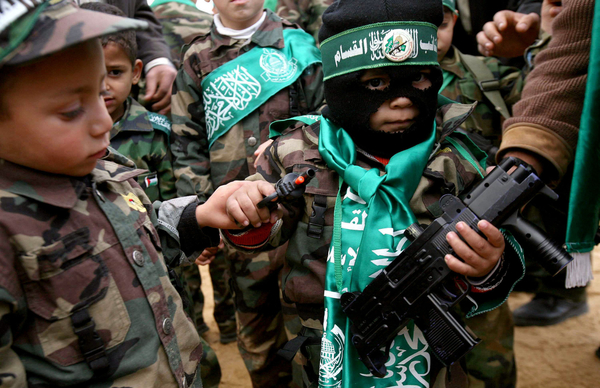 Un niño palestino, vestido como un militante de Hamas, sostiene dos armas de juguete.